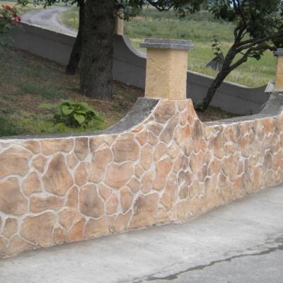 Muro recinzione giardino in intonaco stampato simile a sassi