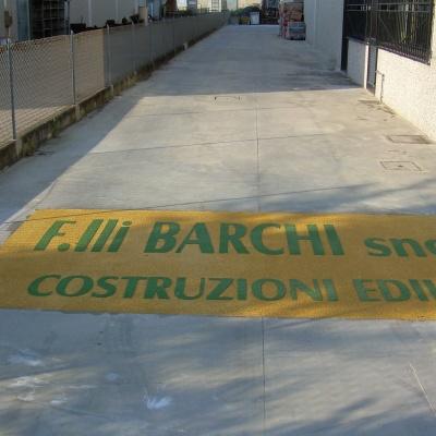 Cortile esterno azienda con logo in cemento spruzzato a Cremona